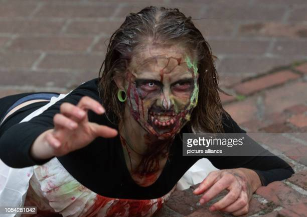 27 October 2018 Germany Berlin A participant of the ZombieWalk lies on a staircase in the Klosterstrasse Photo Paul Zinken/dpa/ZB