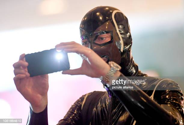 A man in a latex suit photographed at the erotic fair Venus Photo Ralf Hirschberger/dpa