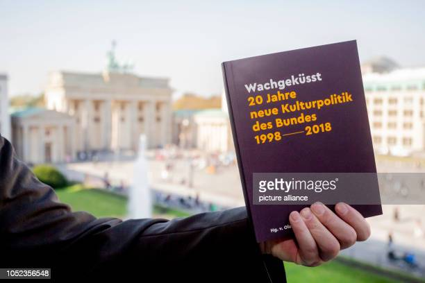 """October 2018, Berlin: The book """"Wachgeküsst. 20 Years of the Confederation's New Cultural Policy 1998-2018"""" with the Brandenburg Gate in the..."""