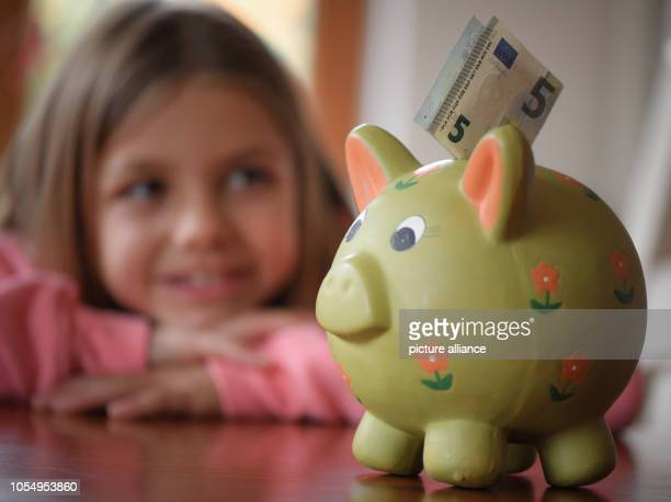 29 October 2018 Brandenburg Sieversdorf Illustration A girl looks at a 5euro bill stuck in a piggy bank 3010 is World Savings Day Photo Patrick...