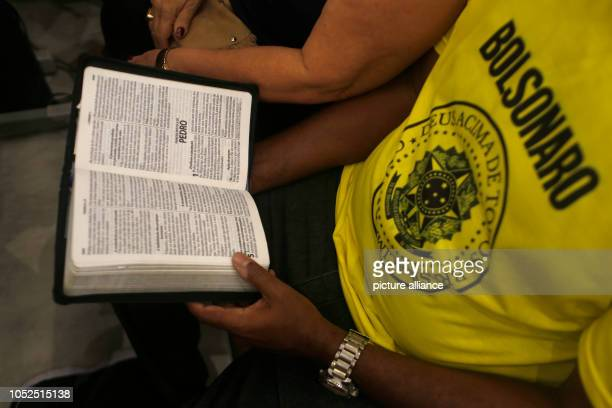 A man with a Tshirt with the inscription 'Bolsonaro' reads the Bible during the last evangelical mass before the election in Brazil Bolsonaro is...