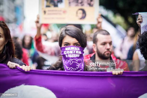 A woman wearing a scarf with the inscription Mulheres contra o fascismo takes part in a demonstration against the extreme rightwing presidential...