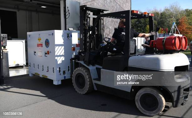 An employee of a transport company uses a forklift to transport the research satellite EuCROPIS to the truck The DLR satellite is to orbit the earth...