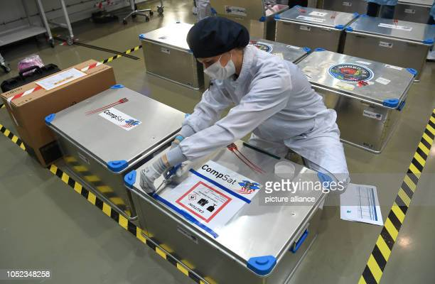 An employee of the German Aerospace Center sticks signs on boxes that travel with the EuCROPIS research satellite The DLR satellite is to orbit the...