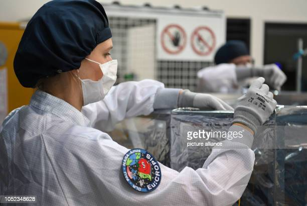 An employee of the German Aerospace Center packages the research satellite EuCROPIS The DLR satellite is to orbit the earth at an altitude of 600...