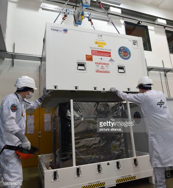 Two employees of the German Aerospace Center pack the research satellite EuCROPIS The DLR satellite is to orbit the earth at an altitude of 600...