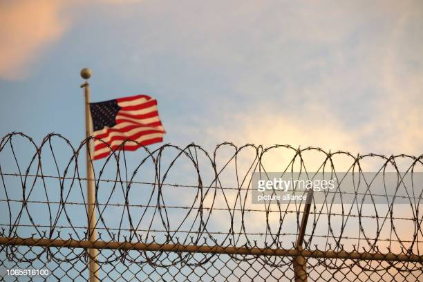 A USAmerican flag blows behind a barbed wire fence in the wind The infamous camp has now existed for almost 17 years 40 inmates are still being held...