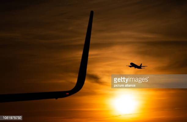 12 October 2018 Germany Hamburg A view of the wing of a passenger aircraft at Hamburg Airport while in the background another aircraft is climbing in...