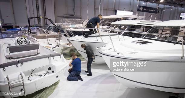 Stand builders are working in the exhibition halls during construction work for the Hamburg Boat Show between small motor yachts at the Jeanneau...