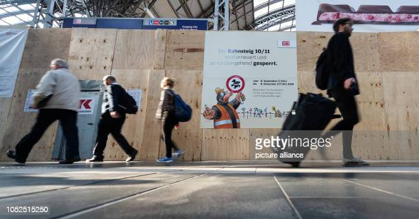 Travellers pass by the construction site of platforms 10 and 11 at Frankfurt Central Station From 8 September to 8 December 2018 the platform to...