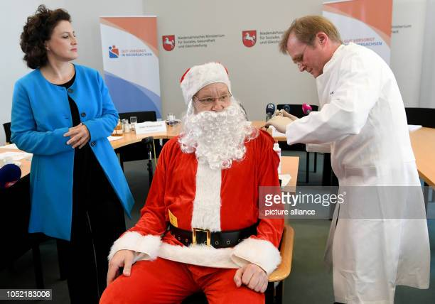 Matthias Pulz President of the State Health Office of Lower Saxony inoculates Santa Claus during a press conference at the start of this year's flu...