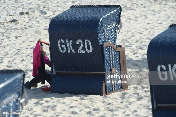 October 2018, Mecklenburg-Western Pomerania, Koserow: A woman sits with a book in her hand in sunny weather at a beach chair on the beach of the...