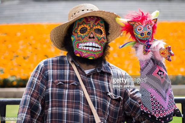 A man wearing a mask at the annual Alejibre Parade in the historic center of Mexico City An Alebrije is a colourful animallike fantasy figure made of...