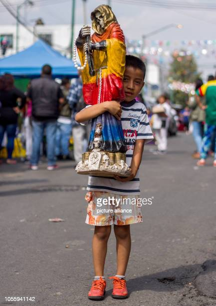 A child carries a statue of the patron saint Santa Muerte to a shrine in the district of Tepito In Mexico City hundreds of supporters made offerings...