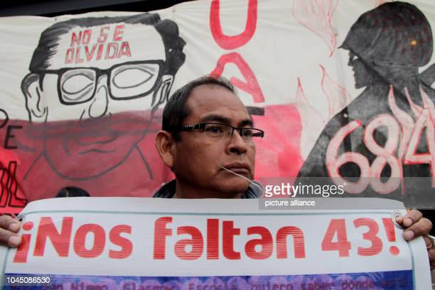 A demonstrator takes part in a march in memory of the victims of a student massacre and shows a poster with the inscription Nos faltan 43 Tens of...