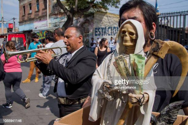 A supporter of Santa Muerte holds a statue of the patron saint in front of a shrine in the Tepito district while a Mariachi musician plays the...