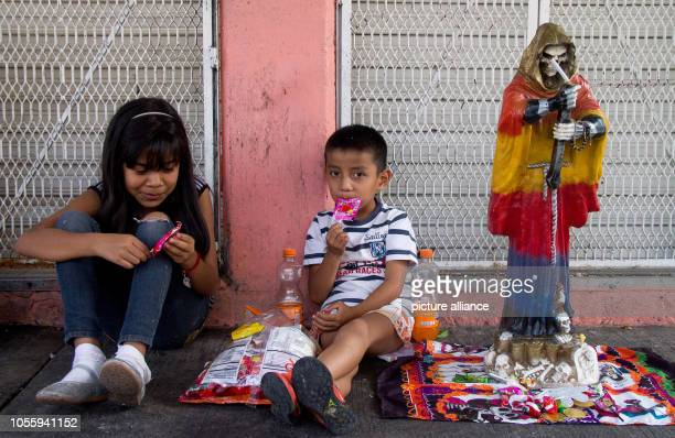 Children eat sweets next to a statue of Santa Muerte in the Tepito district The followers of the patron saints offer Santa Muerte sacrifices such as...