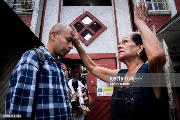 Doña Queta who oversees the shrine of Santa Muerte in the Tepito district prays with a follower of the patron saint In Mexico City hundreds of...