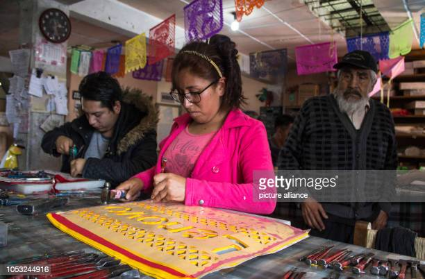 Picadores which can be literally translated as cookie cutters cut out the designs for the colourful garlands by hand with hammer and chisel On the...