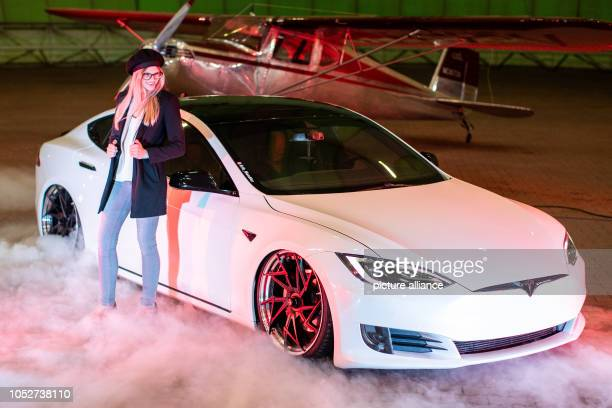 October 2018, North Rhine-Westphalia, Muelheim an der Ruhr: Model Franzi stands in front of a tuned Tesla Model S with 525 HP by Erik Mandler in the...
