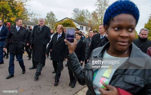 A woman photographs with her mobile phone when Federal Interior Minister Horst Seehofer together with Klaus Bouillon Saarland Minister of the...