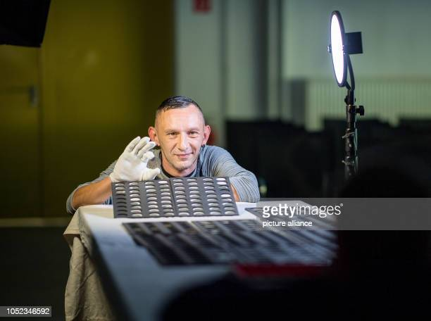 Construction worker Robert Neßler has himself photographed with the coins at a press event to present the coin find at Schloss Lauenstein In July of...