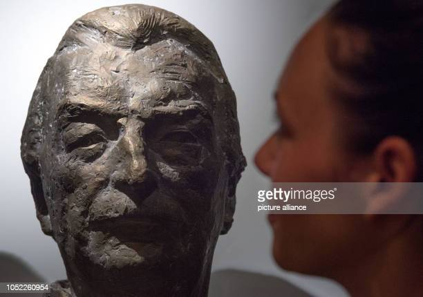 The participant of a preview of the exhibition 'Oh Yeah Pop Music in Germany' looks at a portrait bust of the bandleader James Last in the show at...