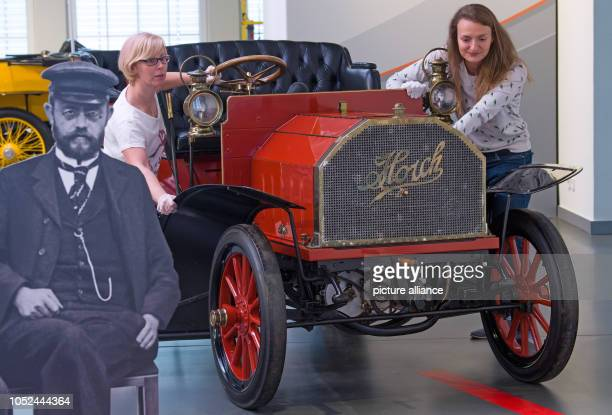 Two employees of the August Horch Museum in Zwickau push a Horch 'Model 2' with 12 HP into position next to a portrait of August Horch The automobile...