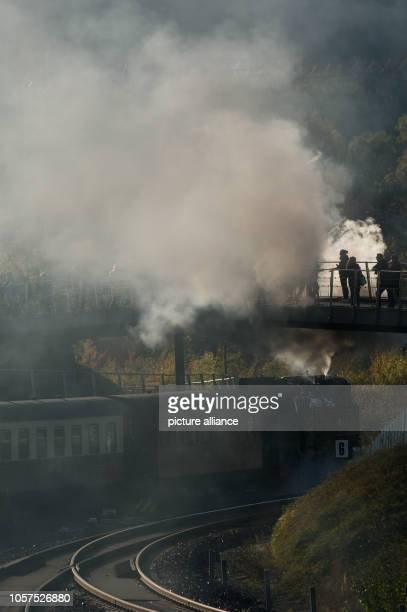 31 October 2018 SaxonyAnhalt Wernigerode Railway enthusiasts visiting the Harz mountains stand on a bridge in front of Wernigerode station while a...