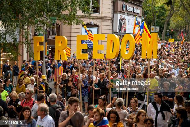 Thousands of people with the words Freedom march from Plaça Catalunya to the Parliament of Catalonia to demand a referendum and democratic rights and...