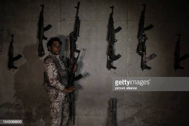 A soldier of the Sham Brigade of the National Liberation Front of Syria holds a gun in a fortified position on front line with forces loyal to Syrian...