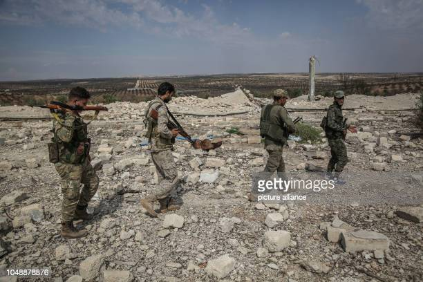 Fighters of the National Front for Liberation patrol the front lines in the northern countryside of the Hama province after the withdrawal of heavy...