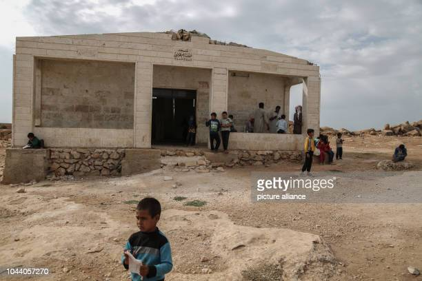 Displaced Syrian children at the yard of a makeshift school built inside an old mosque in the eastern countryside of Idlib province After Seven years...