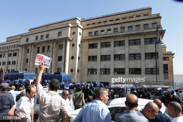 October 2019, Algeria, Algiers: A demonstrator holds a placard in front of police officers standing guard during a protest against a proposed new...