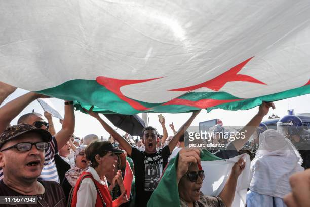 October 2019, Algeria, Algiers: Demonstrators hold a national flag as they take part in a protest against a proposed new hydrocarbons law. Photo:...