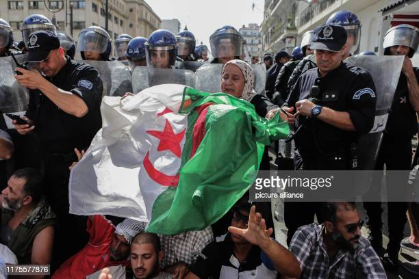Demonstrators shout slogans and hold a national flag in front of police officers during a protest against a proposed new hydrocarbons law Photo...