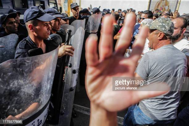 October 2019, Algeria, Algiers: Demonstrators shout slogans in front of police officers standing guard during a protest against a proposed new...