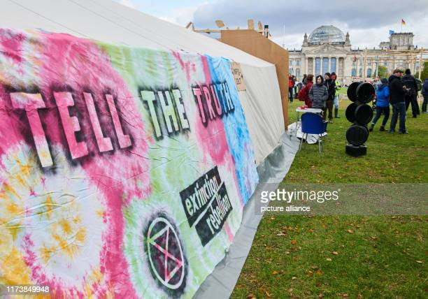 A banner of the climate protection movement hangs on the meadow in front of the Reichstag in the socalled climate camp The construction of the camp...
