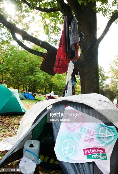 "October 2019, Berlin: A banner with the logos of the climate protection movement Extinction Rebellion hangs on a tent in the so-called ""climate..."
