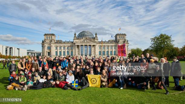 A Swedish group of the climate protection movement Extinction Rebellion places itself on the meadow in front of the Reichstag They're also taking...