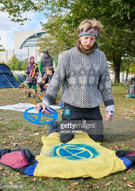 October 2019, Berlin: Jacob examines his sprayed T-shirt with the logo of the climate protection movement Extinction Rebellion. He came all the way...