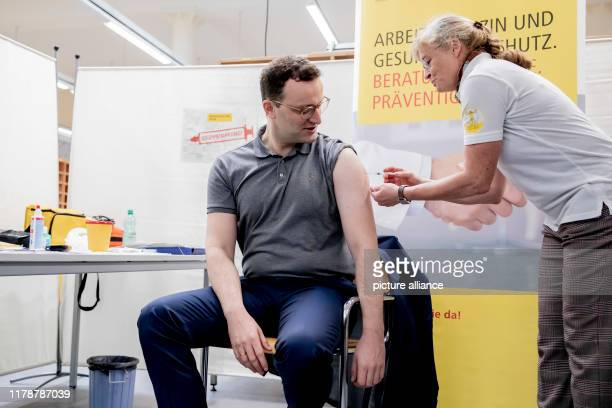 Jens Spahn Federal Minister of Health is vaccinated against influenza by Angelika Haberland a doctor at Deutsche Post DHL Group In addition to the...