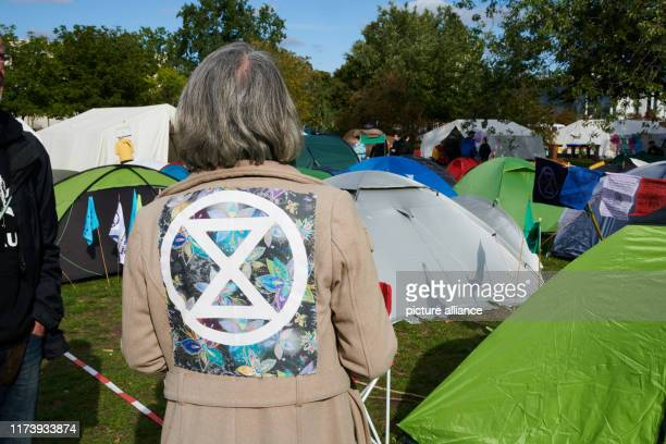 October 2019, Berlin: The logo of the climate protection movement Extinction Rebellion can be seen on the jacket of a woman standing on the protest...