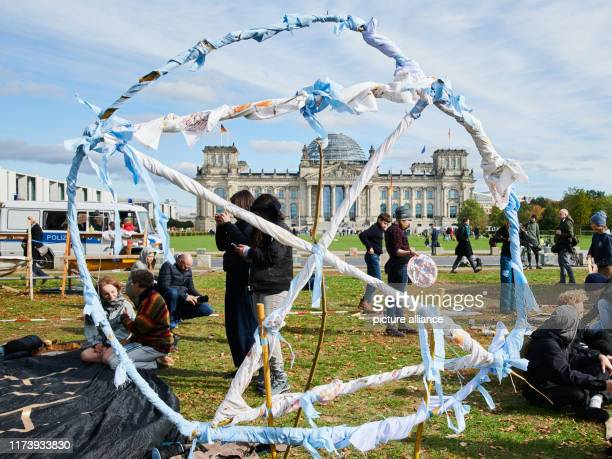 The logo of the climate protection movement Extinction Rebellion stands oversized on the meadow in front of the Reichstag Several thousand...