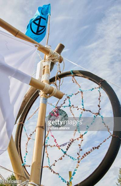 The logo of the climate protection movement Extinction Rebellion blows over an oversized dream catcher at the entrance gate of the protest camp not...