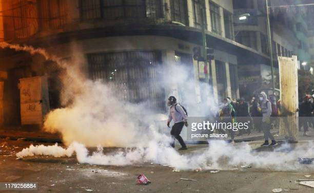 A demonstrator hurls a tear gas canister back against police during clashes Since the results of the presidential elections were announced President...