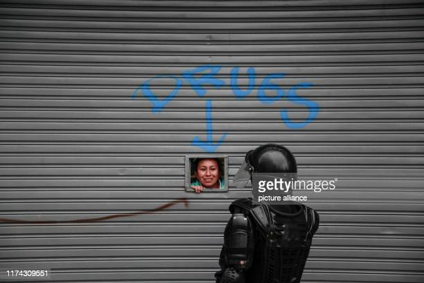 """October 2019, Ecuador, Quito: """"Drugs"""", standing on a roller shutter above a small window through which a woman looks out and is questioned by a..."""
