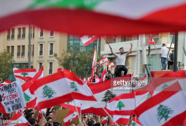 October 2019, Lebanon, Beirut: Thousands of Lebanese demonstrators wave their country's flag during a protest. For the fourth Lebanese are still...