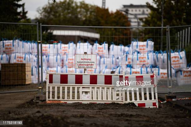 """October 2019, Lower Saxony, Göttingen: A sign """"Attention, explosive ordnance clearance. Danger to life. Trespassing forbidden"""" can be seen in front..."""