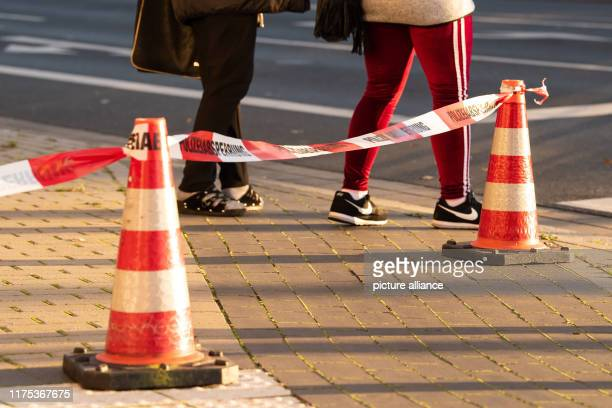 October 2019, Lower Saxony, Göttingen: Passers-by pass a police barrier tape during an evacuation after the discovery of a suspected air raid bomb....